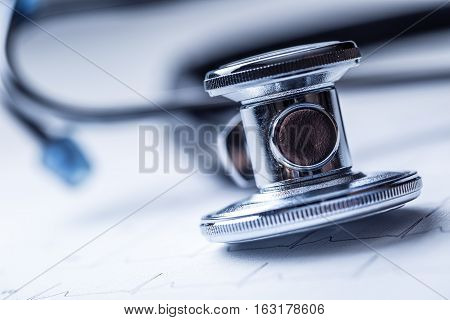 Stethoscope on a heart monitor printout.Electrocardiogram chart and stethoscope.