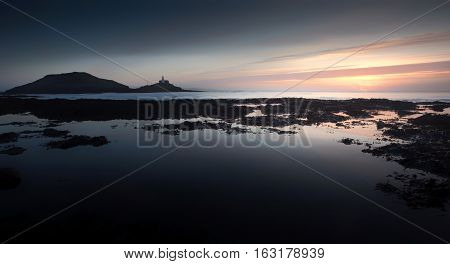 Early morning, big rockpools and Mumbles Lighthouse on a low tide at Bracelet Bay on the Gower peninsula in Swansea, UK