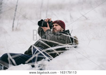 Male photographer taking pictures in winter environment