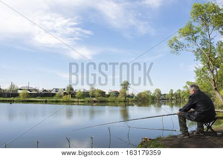 Spring on the lake fisherman with a fishing pole sitting on a chair.