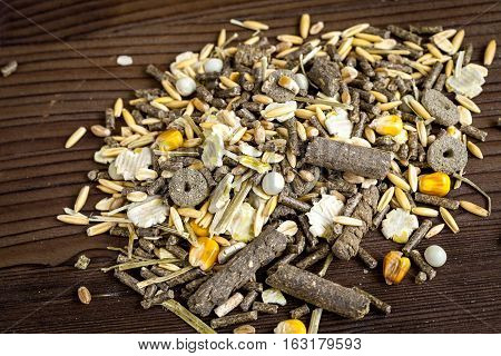 dry food for rodents on dark wooden background