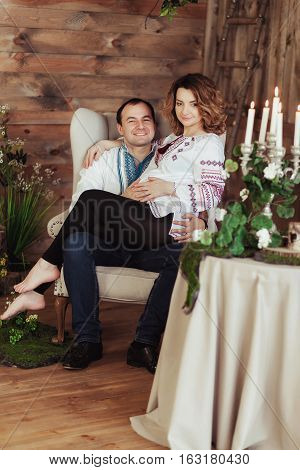 Beautiful young pregnant couple dressed in national ukrainian style in studio. Maternity and family happiness concept.