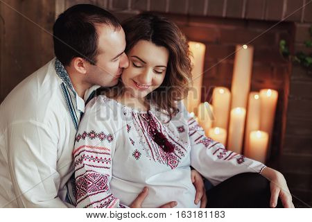 Beautiful young pregnant couple dressed in national ukrainian style sitting by the fireplace with candles. Maternity and family happiness concept.