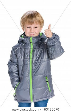 Little Boy In A Coat Holds His Thumb Up