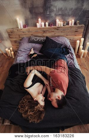 view from the top, young couple embracing in bed, tender. The woman is pregnant.