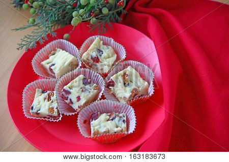 White chocolate candy with dried cranberries and pecans with Christmas greenery and red napkin