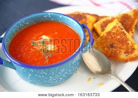 Blue bowl of tomato soup with fresh thyme and a grilled cheese sandwich cut into triangles