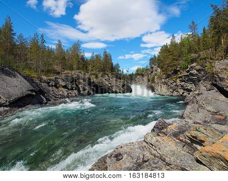 The rapidly flowing river winding through mountains beautiful canyon in Norway summer sunny day