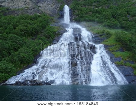 Interesting picturesque waterfall Suitor Geiranger fjord summer day