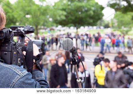 Microphone in focus, cameraman filming blurred crowd