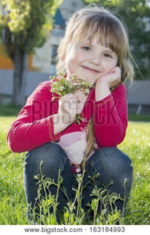 Spring in the park beautiful little girl with pigtails sitting on the grass with a bouquet of flowers.