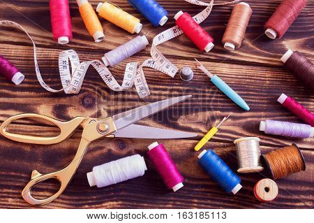 A collection of sewing tools and multi-coloured threads on a wooden background