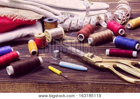A collection of sewing tools and different textile fabric and multi-coloured threads on a wooden brown background