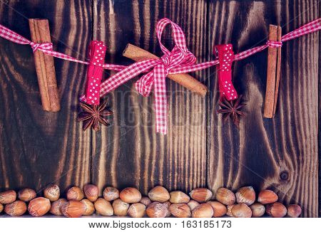 hanging cinnamon and star anises on a rope and hazelnuts on a wooden background