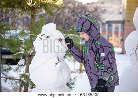 Funny Little Kid Boy Making A Snowman And Eating Carrot, Playing Having Fun With Snow, Outdoors On C