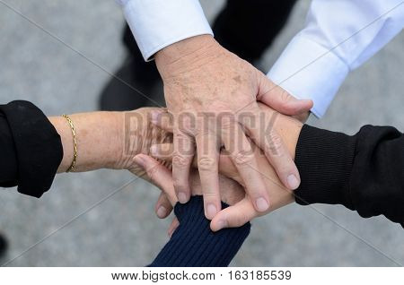 Overhead view of five hands clasped together in a pile representing a diversity of ages
