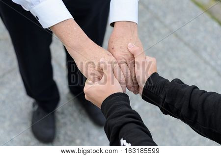 Top down view of hands clasped between friends as one wears a business suit