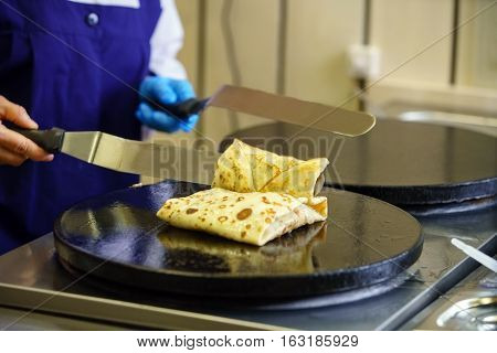 Pancake stuffed by forcemeat with greenery frying in oil on special pan in cafe kitchen