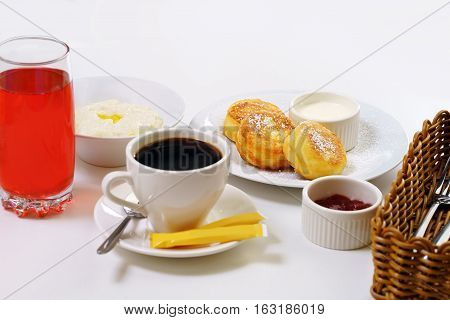 Table set for breakfast with rice porridge, cheesecakes with jam, berry drink and black coffee in cafe