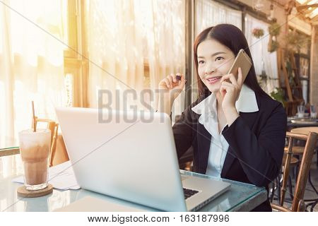 Smiling young asian executive business woman working on her computer and talking on her phone in a coffee shop golden hour lighting coming through the large windows vintage retro style look