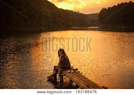 Woman sitting on a pier watching a stunning sunset