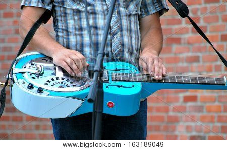Folk musician playing a dobro slide guitar in concert outdoors.