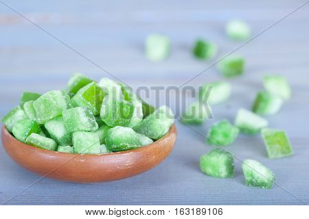 Dried green pomelo squares in wooden bowl