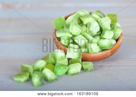 Dried green pomelo fruit in wooden bowl on blue table