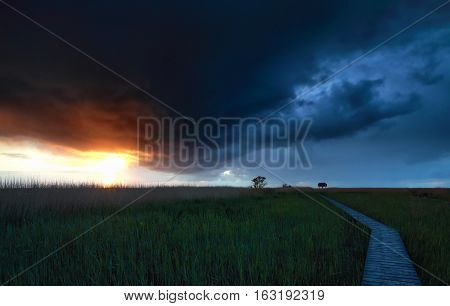 stormy sky over wooden path at sunset Groningen Netherlands