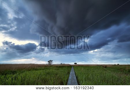 dramatic stormy clouds over pier path on coast