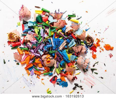 Colorful shavings obtained by sharpening colored pencils, mixed, and on the table.