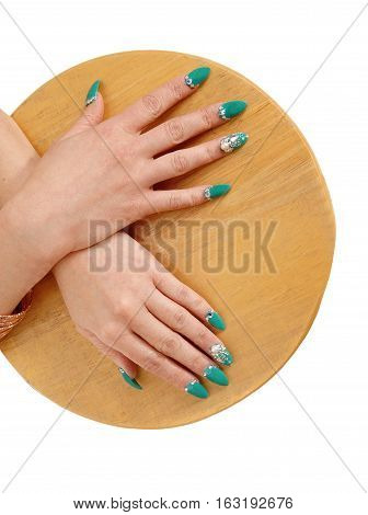 Two hands with beautiful turquoise fingernails on a wood plait isolated for white background.