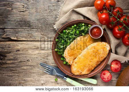 Fried chicken fillet with cheese crust and garnish of fresh vegetables healthy food rustic style