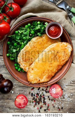 Fried chicken fillet with cheese crust and garnish of fresh vegetables top view