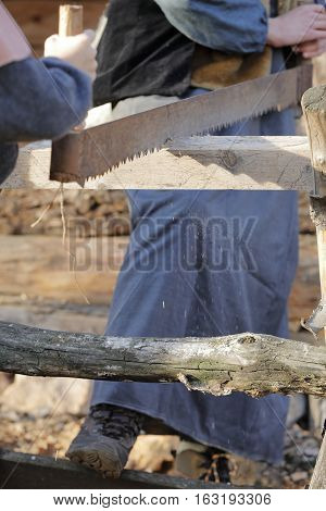 a long carpenter's saw is used by two craftsmen