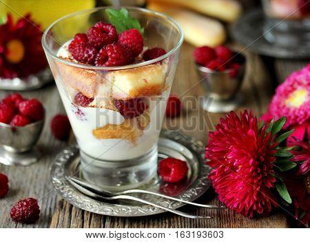 Raspberry tiramisu in glass - romantic dessert on Valentine Day. Raspberry dessert cheesecake trifle on a wooden table with flowers