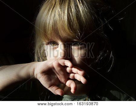 На фото девочка, прикрывающая рот рукой.