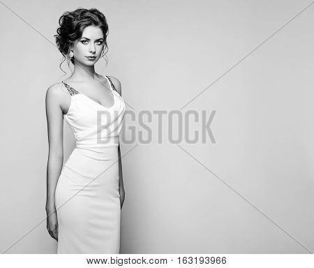 Fashion portrait of beautiful woman in elegant white dress. Girl with elegant hairstyle and jewelry. Black and White