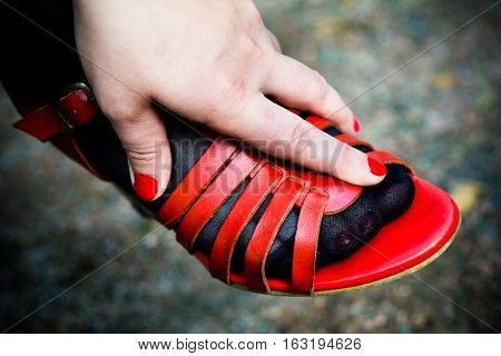 Female hand stuffed in sandals red. The nails are painted with red lacquer.