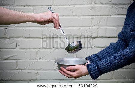 Homeless. In the hands of one man metal plate. In the hand of another person ladle.