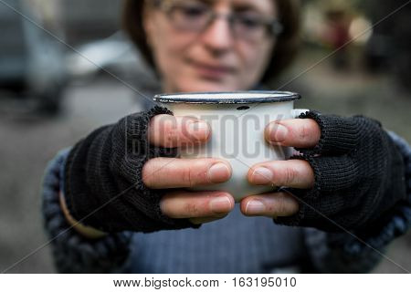 Homeless. In the hands of one man metal bowl. In the hands of black gloves with the fingers cut off.