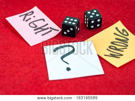 Around black dice are small pieces of paper. On pieces of paper written words and a question mark.