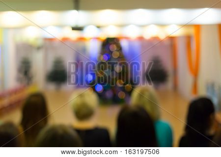 Blurred background Christmas tree and seated people. New year party