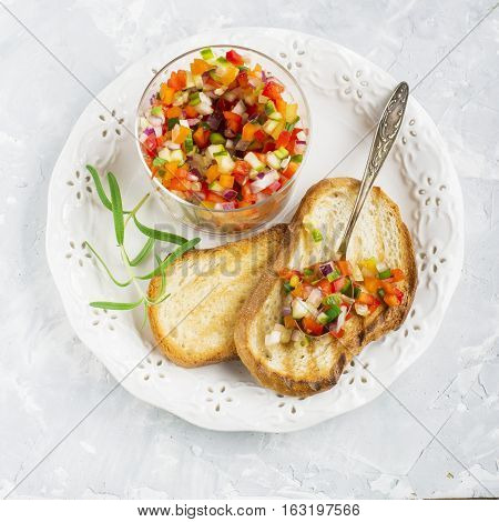 Salad Salsa of colorful vegetables in a glass batch with toasted grilled on a light background. Top view