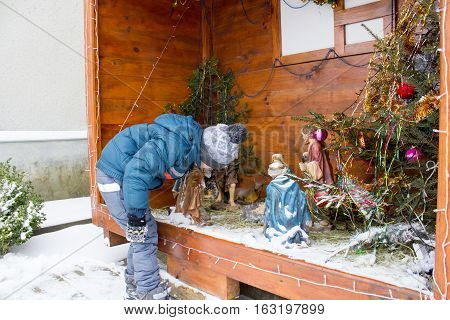 boy stands and looks on the Christmas Nativity Scene