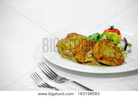 pancakes made from potatoes with a garnish on a plate.
