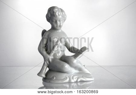 Serial porcelain figurine of an Angel playing a flute from the decor store