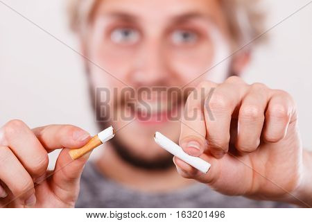Smiling man break down cigarette. Winning with addicted nicotine problems stop smoking. Quitting from addiction concept.