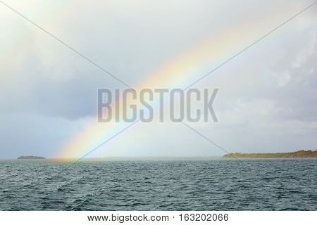 The rainbow above water of Atlantic ocean