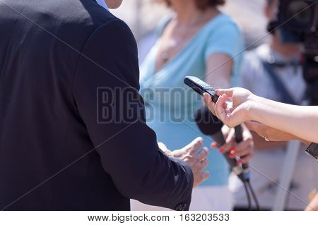 Reporters making interview with businessperson or politician. Press conference.